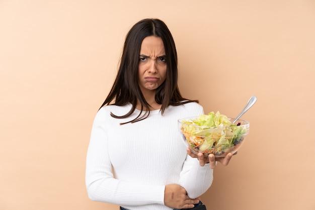 Joven mujer morena sosteniendo una ensalada sentirse molesto