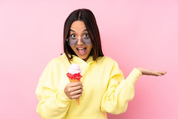 Joven mujer morena sosteniendo un helado de cucurucho con expresión facial sorprendida