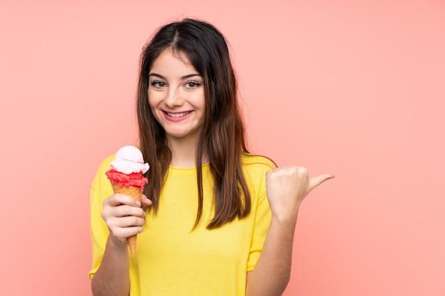 Joven mujer morena sosteniendo un helado de cucurucho sobre pared rosa aislado apuntando hacia un lado para presentar un producto