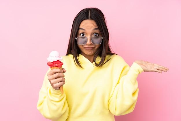 Joven mujer morena sosteniendo un helado de cucurucho teniendo dudas mientras levanta las manos