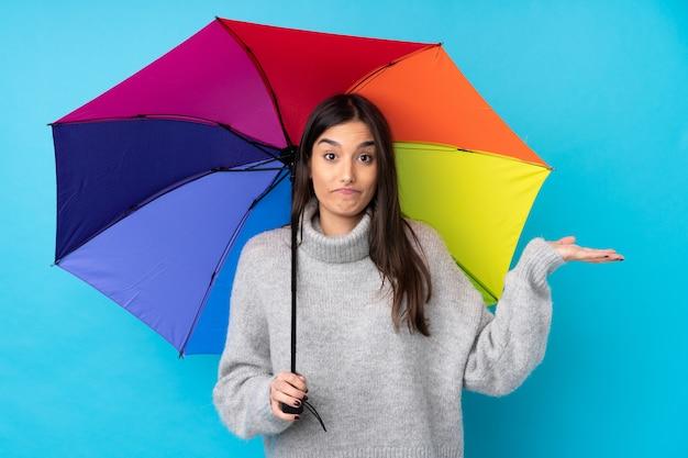 Joven mujer morena sosteniendo un paraguas sobre la pared azul aislada que tiene dudas con confundir la expresión de la cara