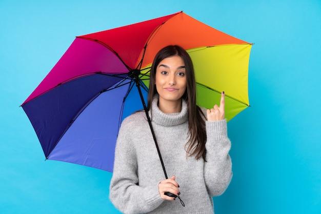 Joven mujer morena sosteniendo un paraguas sobre la pared azul aislada señalando con el dedo índice una gran idea