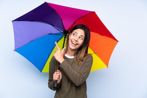 Joven mujer morena sosteniendo un paraguas sobre la pared azul, señalando con el dedo índice una gran idea