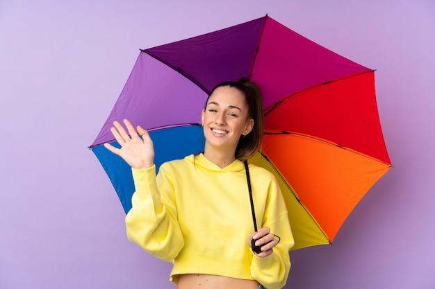 Joven mujer morena sosteniendo un paraguas sobre pared púrpura aislado saludando con la mano con expresión feliz