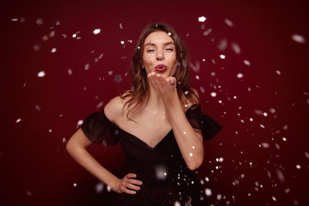 Joven mujer morena vestida con un vestido elegante disfrutando de la fiesta temática de año nuevo mientras posa, levanta la palma y sopla confeti plateado