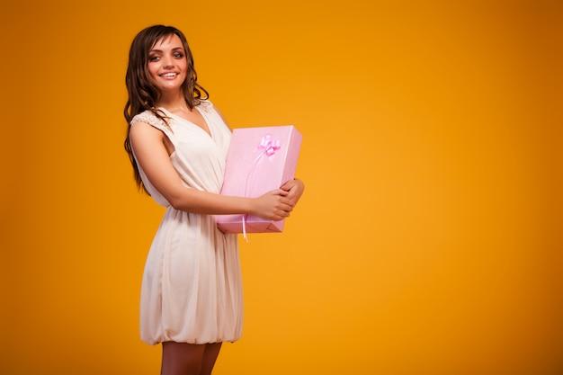 Joven mujer morena en vestido beige de pie, sosteniendo la caja de regalo rosa en las manos y sonriendo sobre fondo amarillo oscuro