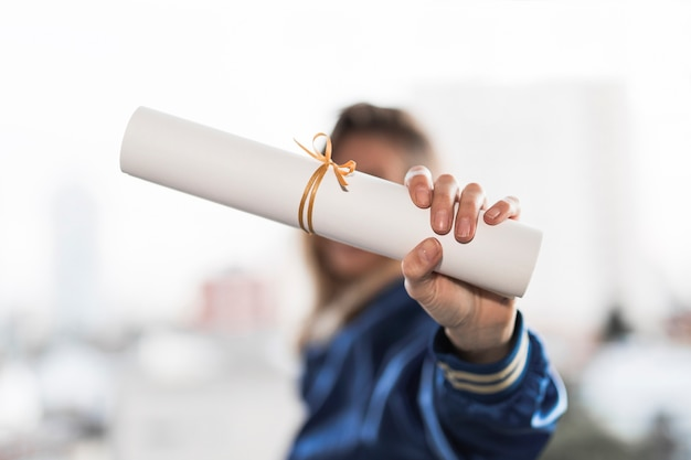 Joven mujer mostrando diploma