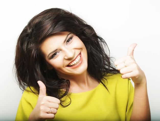 Joven mujer mostrando pulgares arriba gesto