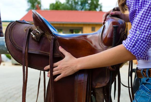 Joven mujer mostrando una silla de montar en la mano