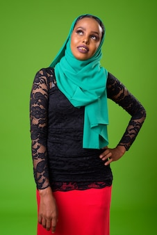 Joven mujer musulmana africana contra chroma key con pared verde