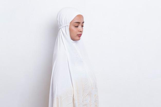 Joven mujer musulmana asiática orando aislado sobre fondo blanco.