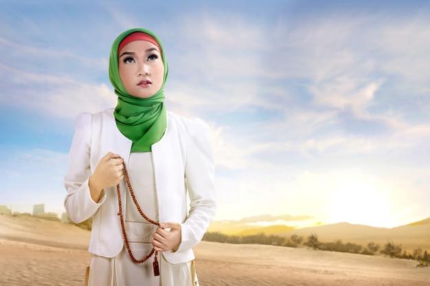 Joven mujer musulmana asiática en velo de pie y rezando con rosarios en la arena