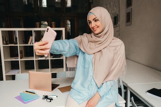 Joven mujer musulmana bastante moderna en hijab trabajando en la computadora portátil en la sala de oficina, educación en línea
