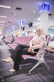 Joven mujer musulmana sonriendo sentado, en la sala de espera de la sala de embarque en el aeropuerto.