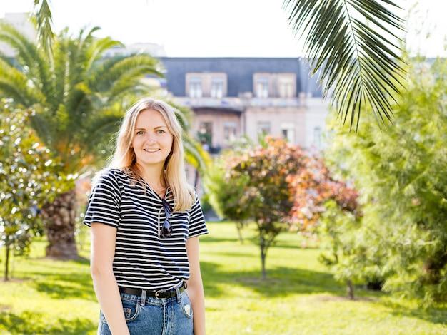 Joven mujer muy atractiva mirando a su alrededor, caminando por la calle de la ciudad tropical con palmeras y coches aparcados, soleado día de verano brillante