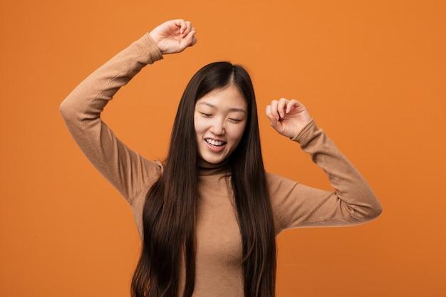 Joven mujer muy china celebrando un día especial, salta y levanta los brazos con energía.