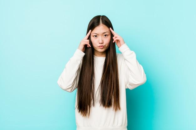 Joven mujer muy china se centró en una tarea, manteniendo los dedos índice apuntando la cabeza.