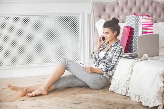 Joven mujer muy hermosa haciendo compras en línea en casa