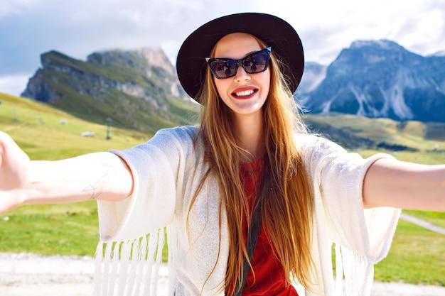 Joven mujer muy de moda haciendo selfie en montañas austriacas