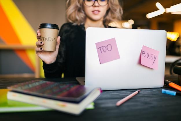 Joven mujer muy ocupada sentada en la mesa trabajando en la computadora portátil en la oficina de co-trabajo, vista cercana, consentimiento, cansado, sosteniendo la taza de café