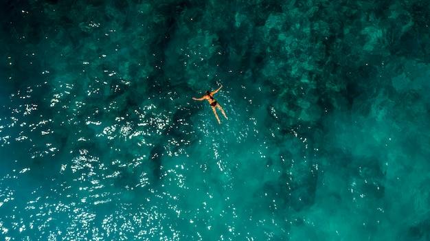 Joven mujer nadando en hermosa vista aérea del océano azul