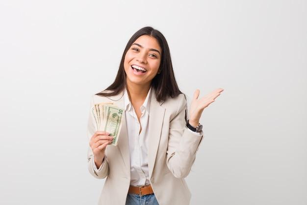 Joven mujer de negocios árabe con dólares celebrando una victoria o éxito