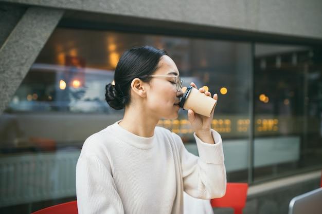 Joven mujer de negocios asiática en gafas está sentado fuera de una cafetería, tomando café