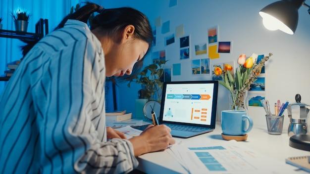 Joven mujer de negocios asiática independiente se centra en la hoja de trabajo de escritura portátil en la computadora portátil en la noche de la casa