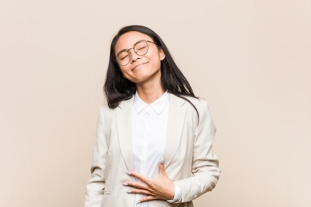 Joven mujer de negocios asiáticos toca barriga, sonríe suavemente