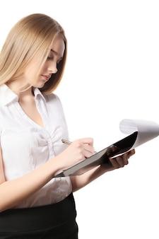 Joven mujer de negocios bonita haciendo notas en un portapapeles sobre fondo blanco.