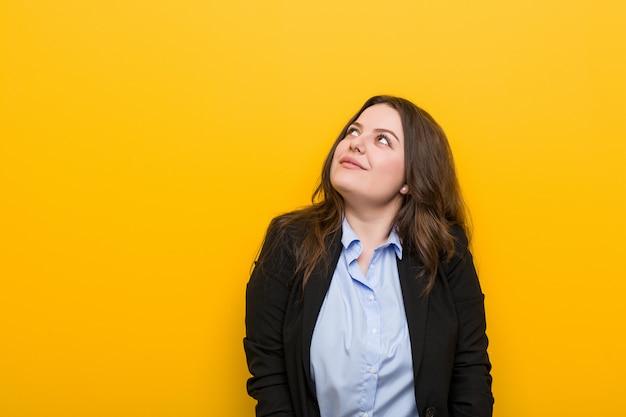 Joven mujer de negocios caucásica de talla grande que sueña con alcanzar metas y propósitos