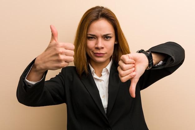 Joven mujer de negocios caucásico mostrando los pulgares hacia arriba y hacia abajo, difícil elegir el concepto