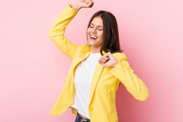 Joven mujer de negocios celebrando un día especial, salta y levanta los brazos con energía.