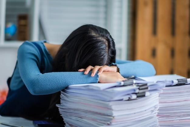 Joven mujer de negocios durmiendo en la mesa de escritorio, trató de mujer atractiva con pila de papeles
