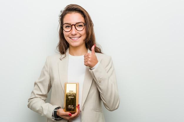 Joven mujer de negocios europea sosteniendo un lingote de oro sonriendo y levantando el pulgar
