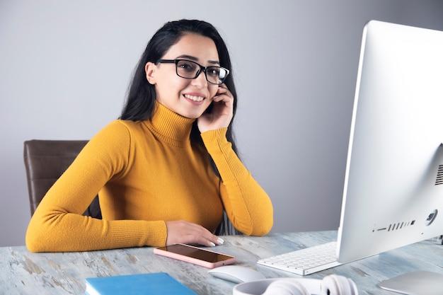 Joven mujer de negocios feliz en el escritorio de oficina