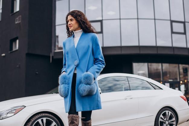 Joven mujer de negocios feliz saliendo de su coche