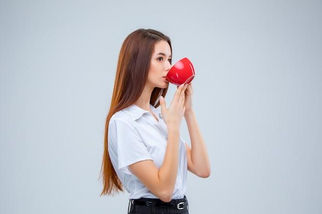 La joven mujer de negocios i con rojo taza de café en un espacio gris