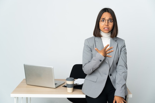 Joven mujer de negocios latina que trabaja en una oficina aislada sobre fondo blanco apuntando a uno mismo