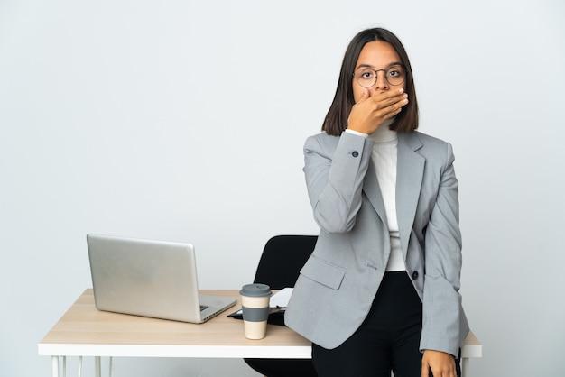 Joven mujer de negocios latina que trabaja en una oficina aislada sobre fondo blanco cubriendo la boca con la mano
