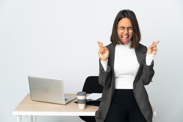 Joven mujer de negocios latina que trabaja en una oficina aislada sobre fondo blanco con los dedos cruzados