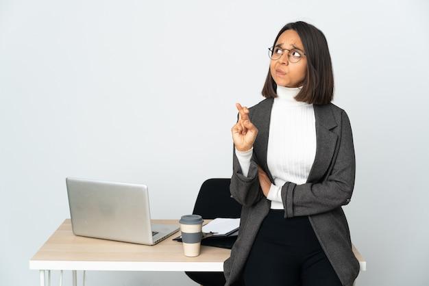Joven mujer de negocios latina que trabaja en una oficina aislada sobre fondo blanco con los dedos cruzando y deseando lo mejor