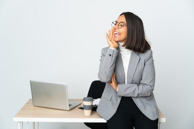 Joven mujer de negocios latina que trabaja en una oficina aislada sobre fondo blanco gritando con la boca abierta hacia un lado