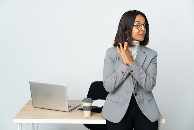 Joven mujer de negocios latina que trabaja en una oficina aislada sobre fondo blanco maquinando algo