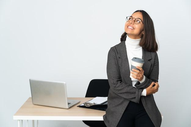 Joven mujer de negocios latina que trabaja en una oficina aislada sobre fondo blanco mirando hacia arriba mientras sonríe
