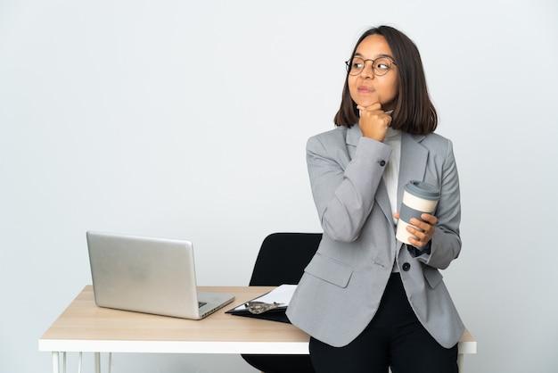 Joven mujer de negocios latina que trabaja en una oficina aislada sobre fondo blanco pensando en una idea mientras mira hacia arriba