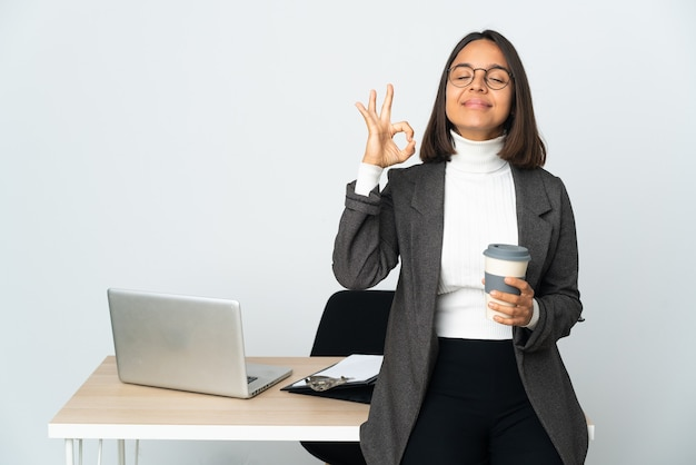 Joven mujer de negocios latina que trabaja en una oficina aislada sobre fondo blanco en pose zen