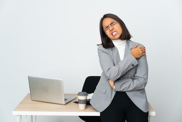 Joven mujer de negocios latina que trabaja en una oficina aislada sobre fondo blanco que sufre de dolor en el hombro por haber hecho un esfuerzo