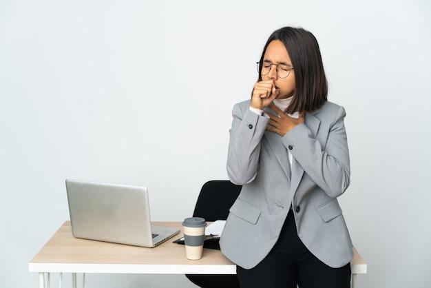 Joven mujer de negocios latina que trabaja en una oficina aislada sobre fondo blanco tosiendo mucho