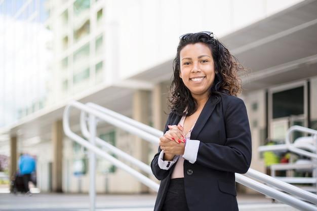Joven mujer de negocios latinoamericana con gesto de confianza. ella está al aire libre y con ropa elegante. espacio para texto.